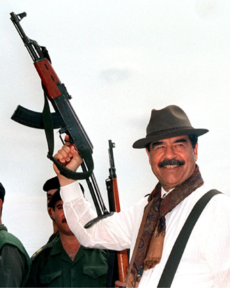 Saddam Hussein brandishing a Russian-made AK 47 assault rifle during his visit to villages in northern Iraq. (AFP)