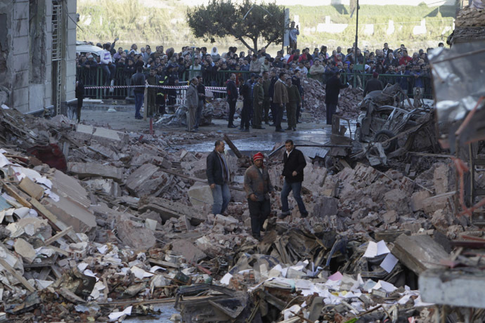 People walk near debris after an explosion near the Building of the Directorate of Security in Egypt's Nile Delta town of Dakahlyia, about 120 km (75 miles) northeast of Cairo December 24, 2013. (Reuters/Mohamed Abd El Ghany)
