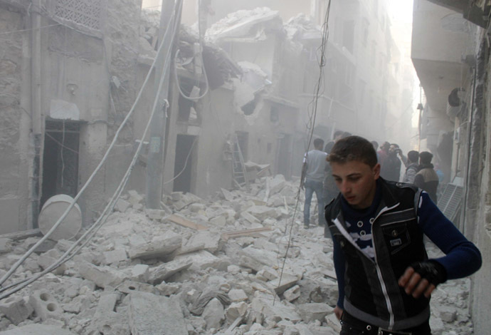 People stand on the rubble of damaged buildings after what activists said was an air raid by forces loyal to Syrian President Bashar Al-Assad, in Aleppo's al-Saliheen district December 23, 2013. (Reuters/Saad AboBrahim)