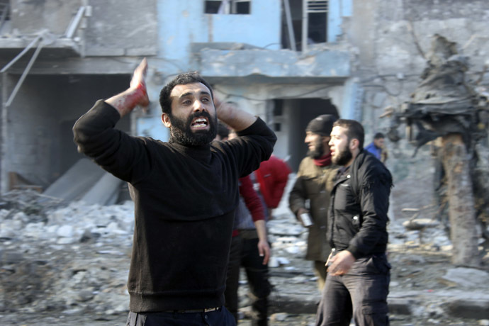 A man with blood stained hand reacts at a damaged site after what activists said was heavy shelling by forces loyal to Syrian President Bashar Al-Assad, in Masaken Hanano neighbourhood in Aleppo December 22, 2013. (Reuters/Hosam Katan)