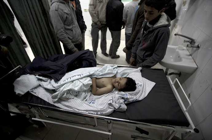 The brother of killed three-year-old Palestinian girl Hala Abu Sabikha, lies on a hospital trolley in Deir al-Balah, in the central Gaza Strip, on December 24, 2013. (AFP Photo / Mahmud Hams)