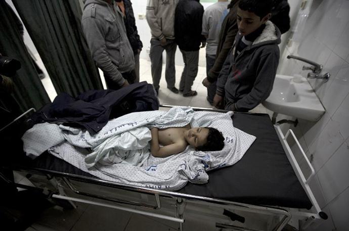 The brother of killed three-year-old Palestinian girl Hala Abu Sabikha, lies on a hospital trolley in Deir al-Balah, in the central Gaza Strip, on December 24, 2013. (AFP Photo / Mahmud Hams)
