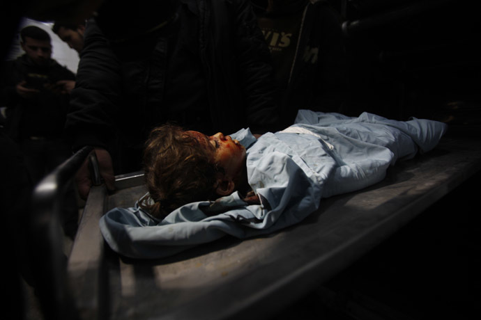 The body of three-years-old Palestinian girl Hala Bhairi, who medics said was killed by shrapnel during an Israeli air strike on the Bureij facility, lies at a hospital morgue in the central Gaza Strip December 24, 2013. (Reuters/Ibraheem Abu Mustafa)