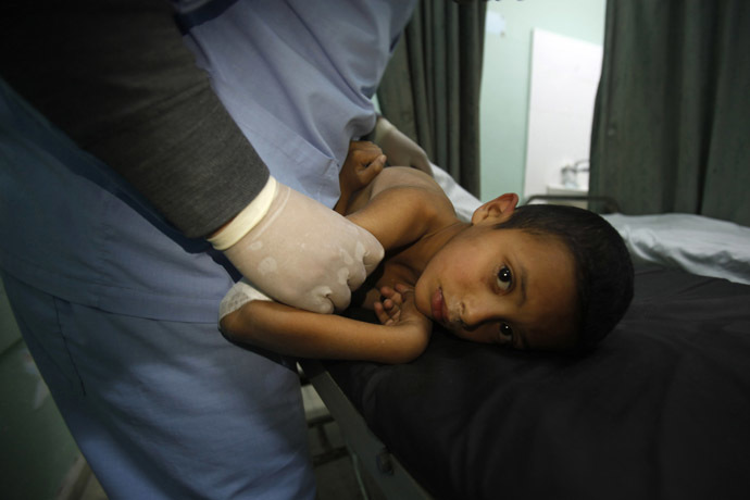 A Palestinian boy, who medics said was wounded during an Israeli air strike on the Bureij facility, lies on a bed at a hospital in the central Gaza Strip December 24, 2013. (Reuters/Ibraheem Abu Mustafa)
