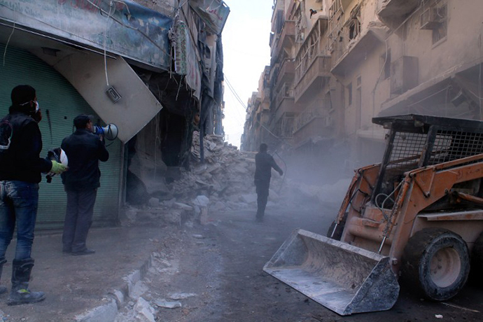 A digger arrives to remove the rubble following an airstrike in the northern Syrian city of Aleppo on December 24, 2013. (AFP Photo / Fouad Hallak)