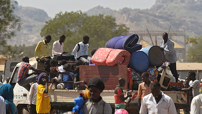 Residents of Juba with their belongings pile onto a truck heading out of the city on December 21, 2013 where tension remains high fueling an exodus of both local and foreign residents from the south Sudanese capital. (AFP Photo / Tony Karumba)