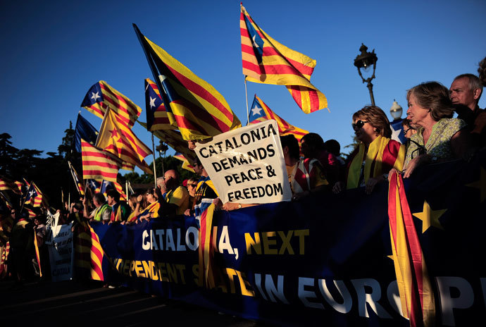 Demonstrators hold a giant banner and Catalan independentist flags during a protest as part of a campaign for independence from Spain.(AFP Photo / Josep Lago)