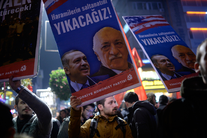 """A Turkish protester holds up a placard with pictures of Turkish Prime Minister Recep Tayyip Erdogan (L) and the United States-based Turkish cleric Fethullah Gulen reading """"We will cast them down"""" during a demonstration against corruption in the Kadikoy district of Istanbul on December 25, 2013 (AFP Photo / Bulent Kilic)"""