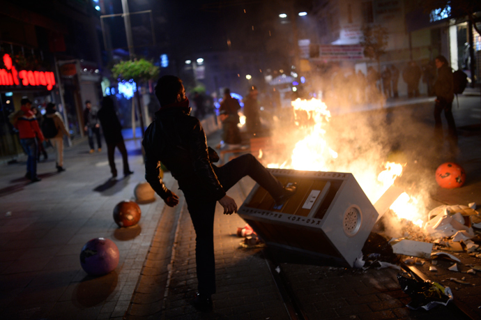 A man helps build a barricade as demonstrators clash with riot police (unseen) during a protest against corruption in the Kadikoy district of Istanbul on December 25, 2013 (AFP Photo / Bulent Kilic)