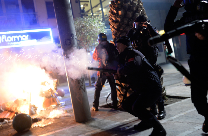 Turkish riot police fire tear gas at protestors (unseen) during a demonstration against corruption in the Kadikoy district of Istanbul on December 25, 2013 (AFP Photo / Bulent Kilic)