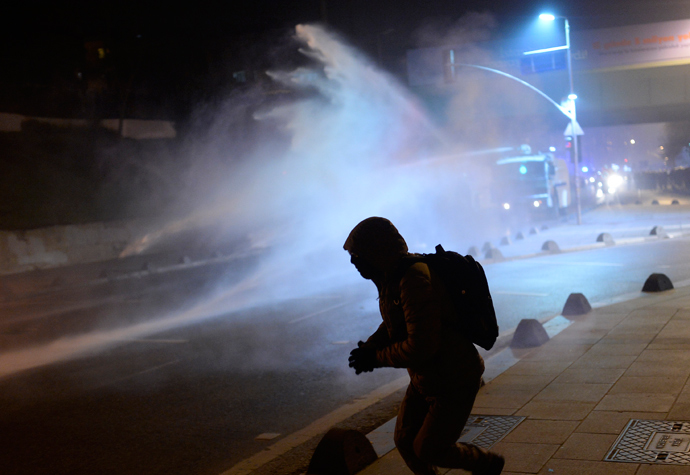 A demonstrator runs away after throwing a projectile toward riot police spraying tear gas during a demonstration against corruption in the Kadikoy district of Istanbul on December 25, 2013 (AFP Photo / Bulent Kilic)