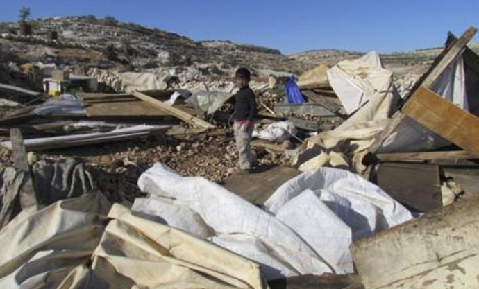 A Bedouin refugee child standing on the site of his demolished home. Image from UNRWA