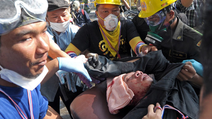 Thai anti government protesters carry an injured from gunshot during a rally at a stadium to register party-list candidates in Bangkok on December 26, 2013. (AFP Photo / Pornchai Kittiwongsakul)
