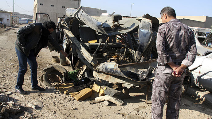 An Iraqi policeman looks at a damaged vehicle after a car bomb attack in Baghdad. December 16, 2013 (Reuters / Wissm al-Okili)