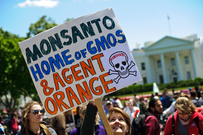 People hold signs during a demonstration against agribusiness giant Monsanto and genetically modified organisms (GMO) in front of the White House in Washington on May 25, 2013. (AFP Photo/Nicholas Kamm)