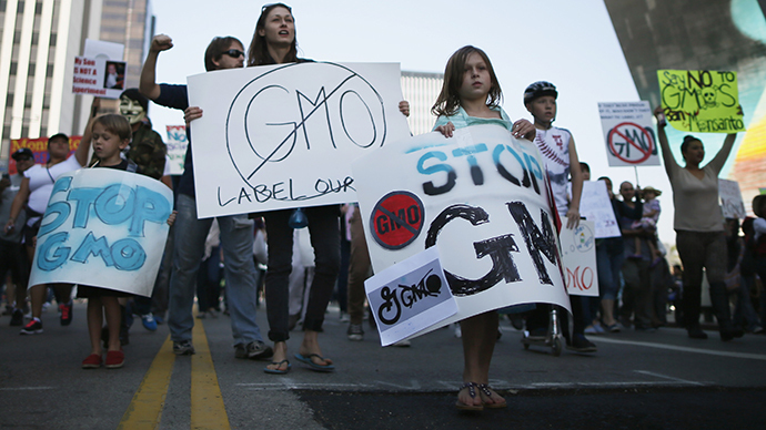 """People hold signs during one of many worldwide """"March Against Monsanto"""" protests against Genetically Modified Organisms (GMOs) and agro-chemicals, in Los Angeles, California October 12, 2013. (Reuters / Lucy Nicholson)"""