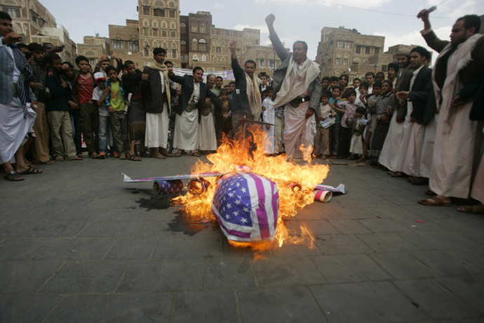 Protesters loyal to the Shi'ite al-Houthi rebel group burn an effigy of a U.S. aircraft during a demonstration to protest against what they say is U.S. interference in Yemen, including drone strikes, after their weekly Friday prayers in the Old Sanaa city April 12, 2013. (Reuters/Khaled Abdullah)