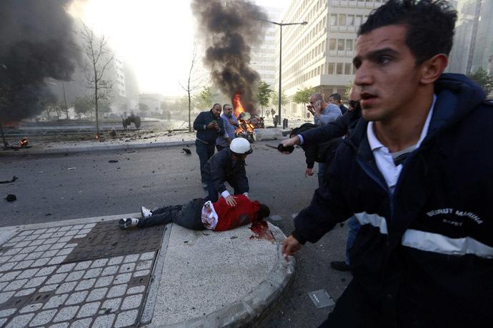 As pessoas correm para ajudar um homem ferido como a fumaça sobe do local de uma explosão no centro da cidade de Beirute 27 de dezembro de 2013.  (Reuters / Jamal Saidi)