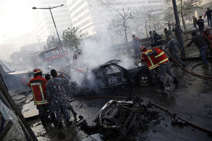 Civil Defence personnel extinguish fires on cars at the site of an explosion in Beirut downtown area December 27, 2013. (Reuters/Steve Crisp)