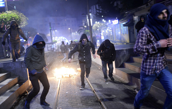 Demonstrators run away as they clash with riot police (unseen) during a protest against corruption in the Kadikoy district of Istanbul on December 25, 2013. (AFP Photo/Bulent Kilic)