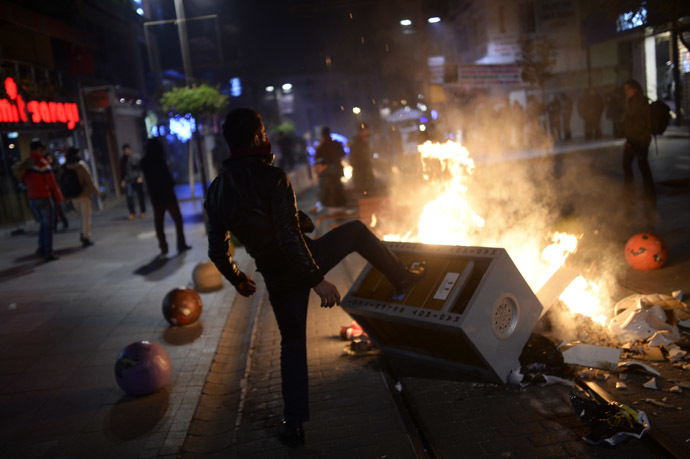 A man helps build a barricade as demonstrators clash with riot police (unseen) during a protest against corruption in the Kadikoy district of Istanbul on December 25, 2013. (AFP Photo/Bulent Kilic)