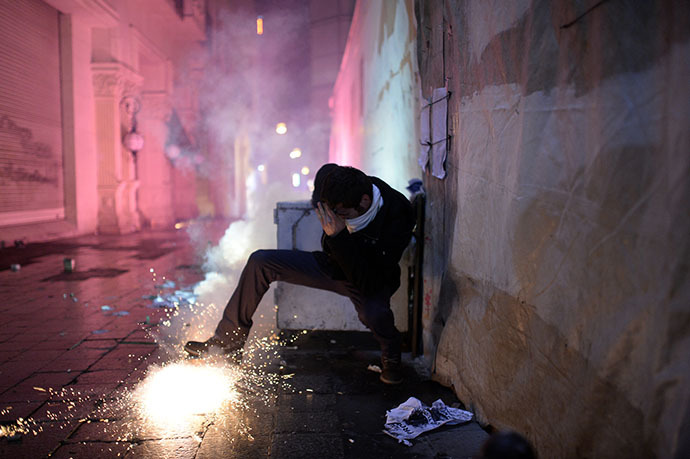 A protestor protects himself as fireworks explode on the Istiklal Avenue on December 27, 2013, during clashes between the Turkish police and protestors. (AFP Photo / Bulent Kilic)