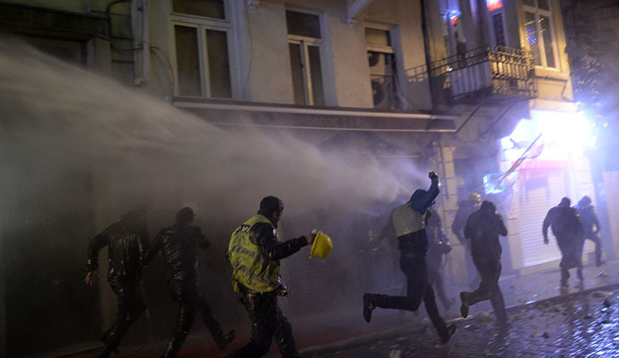 Protesters run from a water cannon on the Istiklal Avenue on December 27, 2013, during clashes between the Turkish police and protestors. (AFP Photo / Bulent Kilic)