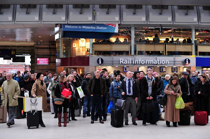 People wait under departure boards at Waterloo train station in central London as disruption to rail services continues on December 24, 2013. (AFP Photo / Carl Court)