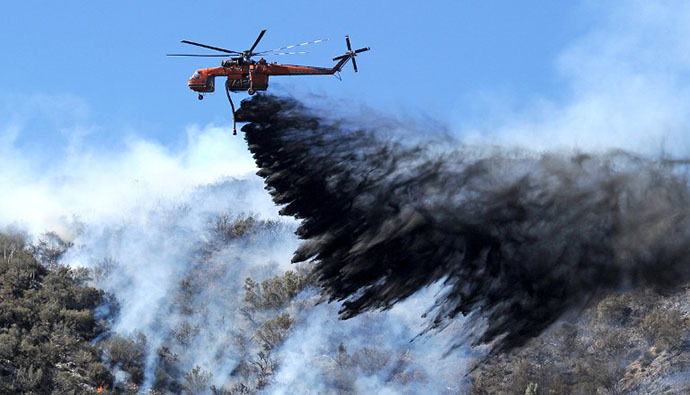 A firefighting helicopter drops fire retardant on a flare up at the Powerhouse Fire, near Lake Hughes, California, approximately 66 miles (100 km) north of Los Angeles June 3, 2013. (AFP Photo / Robyn Beck)