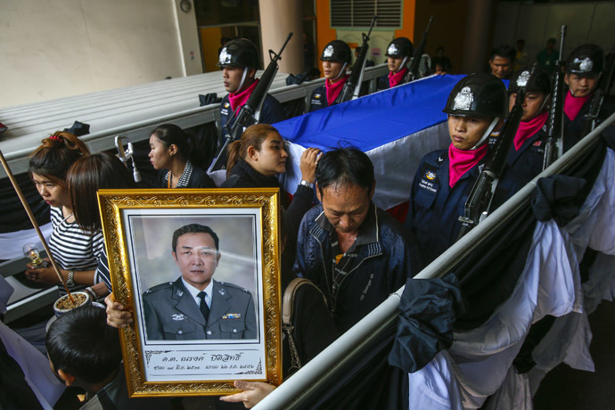Relatives and mourners lead a procession to a temple for the funeral ceremony of Narong Pitisitthi, 45, a policeman who died after being shot during the clashes between anti-government protesters and riot police, at the police hospital in Bangkok December 27, 2013. (Reuters/Athit Perawongmetha)