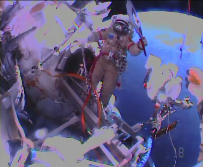 Russian astronaut Oleg Kotov holds an Olympic torch as he begins a spacewalk outside the International Space Station in this still image taken from video courtesy of NASA TV, November 9, 2013. (Reuters/NASA)
