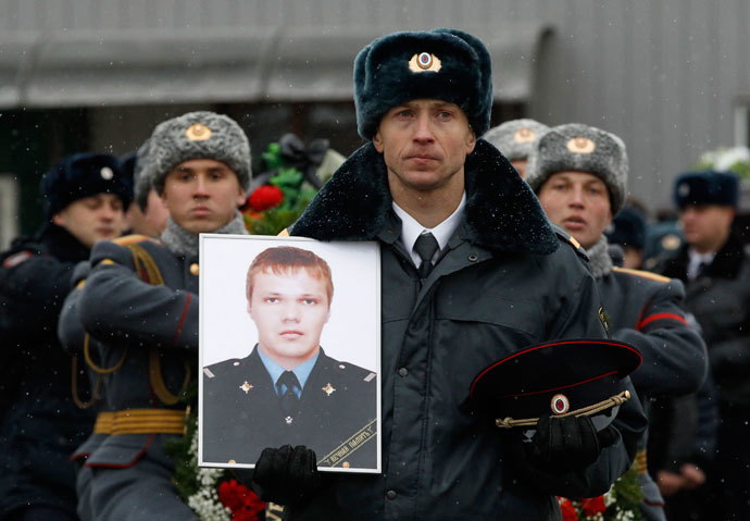 A police officer carries a portrait of Russian police senior sergeant Dmitry Makovkin who was killed by a suicide bomb blast in the city main railway station, in front of the funeral procession carrying Makovkin's coffin in Volgograd, January 2, 2014.(Reuters / Vasily Fedosenko)