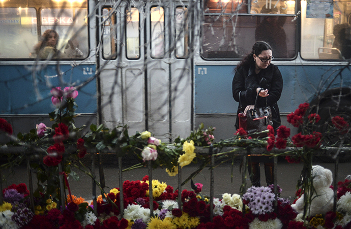 A woman reacts while standing near flowers placed at the site of an explosion on a trolleybus in Volgograd December 31, 2013. (Reuters / Sergei Karpov)