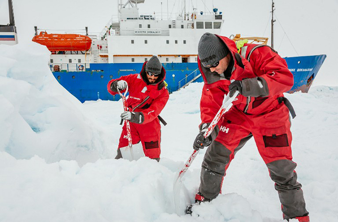 This image taken by expedition doctor Andrew Peacock of www.footloosefotography.com on December 31, 2013 shows scientists from the University of New South Wales in Australia, Ziggy Marzinellia and Graeme Clark, preparing a suitable surface for a helicopter landing next to the MV Akademik Shokalskiy (background), still stuck in the ice off East Antarctica. (AFP Photo)