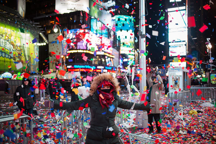 Valentina Guazzolini, of Ravenna, Italy, plays in confetti which was scattered by a gust of wind into the air after New Year celebrations in Times Square, Midtown, New York January 1, 2014.(Reuters / Adrees Latif)