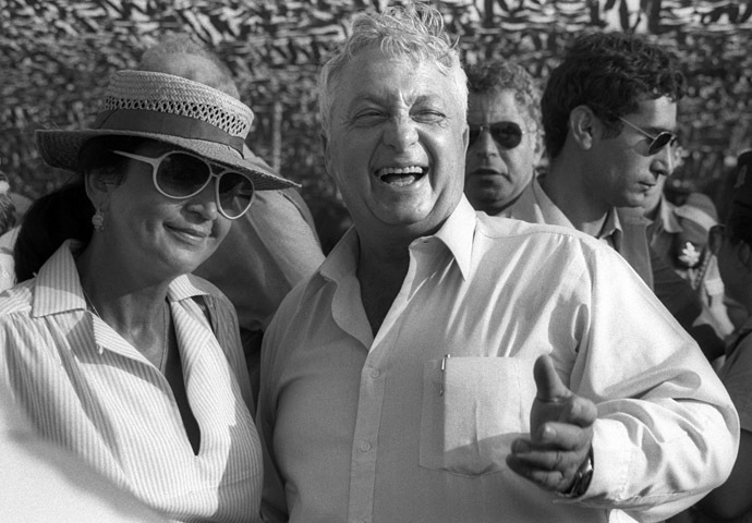 Ariel Sharon laughs as his wife Lily stands at his side during an aerial display in an Israeli Air Force Base July 15, 1982 in this handout photo released by the Government Press Office. (Reuters/Baruch Rimon/Government Press Office)