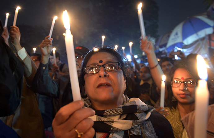 Indian activists hold candles as they participate in a mass meeting to protest against the gangrape and murder of a teenager in Kolkata on January 2, 2014. (AFP Photo / Dibyangshu Sarkar)