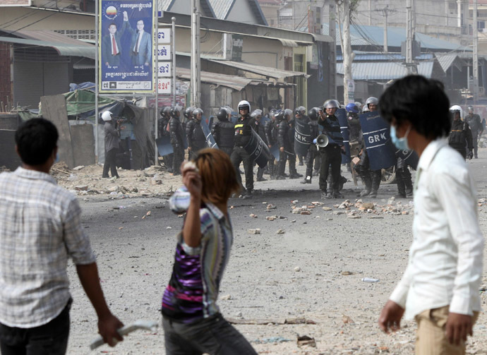 A worker throws a stone after clashes broke out during a protest in Phnom Penh January 3, 2014. (Reuters/Samrang Pring)