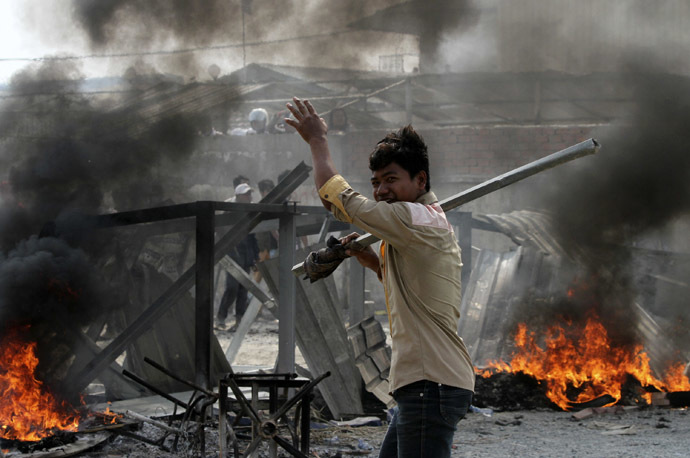 A worker carrying a metal rod reacts after clashes broke out during a protest in Phnom Penh January 3, 2014. (Reuters/Samrang Pring)