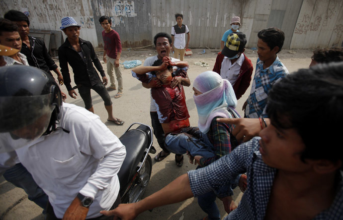 An injured garment worker is helped by his colleagues after clashes broke out during a protest in Phnom Penh January 3, 2014. (Reuters/Samrang Pring)