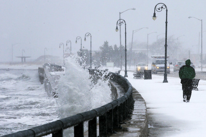 A man jogs past waves crashing against the seawall around high tide during a winter nor'easter snowstorm in Lynn, Massachusetts January 2, 2014. (Reuters/Brian Snyder)