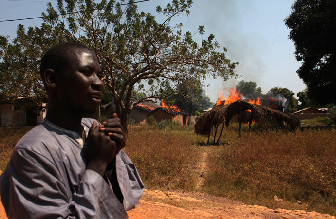 A man walks past burning houses in Bossangoa, north of Bangui January 2, 2014. (Reuters/Andreea Campeanu)