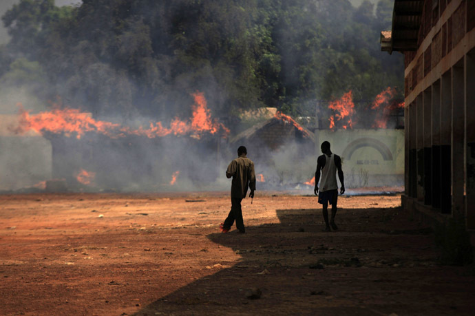Youths walk towards burning houses in Bossangoa, north of Bangui January 2, 2014. (Reuters/Andreea Campeanu)