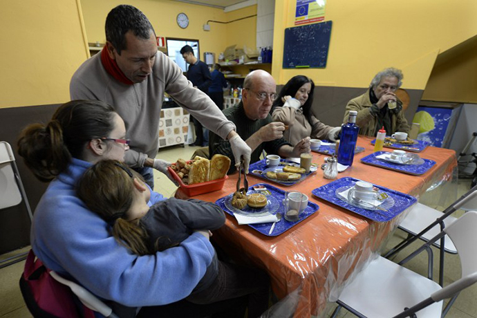 People have breakfasts at a soup kitchen in Barcelona on December 17, 2013. For the past three years, the soup kitchen has been serving up hot breakfasts to the needy. Unlike most of Spain's economy, it is experiencing high demand. (AFP Photo / Llius Gene)