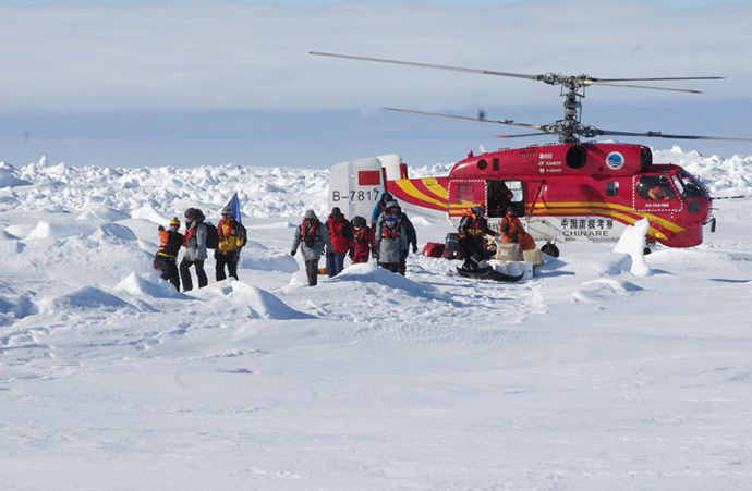 This photo released by the Australian Antarctic Division on January 2, 2014 shows a rescue worker (L) directing passengers who spent Christmas and New Year trapped on the icebound Russian research vessel Akademik Shokalskiy in Antarctica after they disembarked from a rescue helicopter from the Chinese ship Xue Long (R), after they were airlifted from the ice in a dramatic rescue mission. (AFP Photo / Jessica Fitzpatrick)