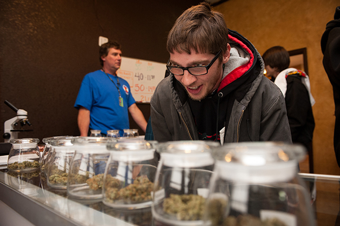 Tyler Williams of Blanchester, Ohio selects marijuana strains to purchase at the 3-D Denver Discrete Dispensary on January 1, 2014 in Denver, Colorado. (AFP Photo / Getty Images / Theo Stroomer)