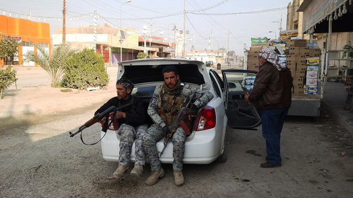 Armed tribesmen and Iraqi police sit in a car as clashes rage on in the Iraqi city of Ramadi, west of Baghdad, on January 2, 2014. (AFP Photo / Azhar Shallal)