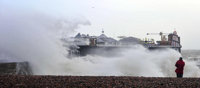 A man photographs Brighton Pier in southern England in southern England on January 3, 2014 as waves strike after a high tide. (AFP Photo/Carl Court)