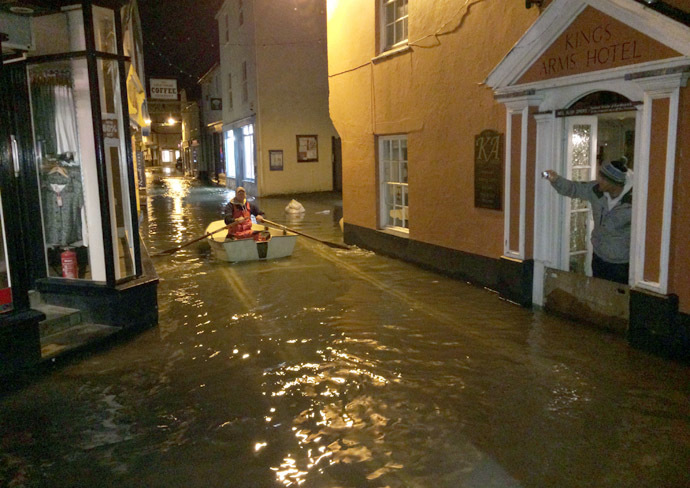 This handout picture received from the Royal National Lifeboat Institution (RNLI) on January 3, 2014 shows a man rowing a boat down the flooded main street following a high tide at Salcombe in Devon, southwest England. (AFP/RNLI)