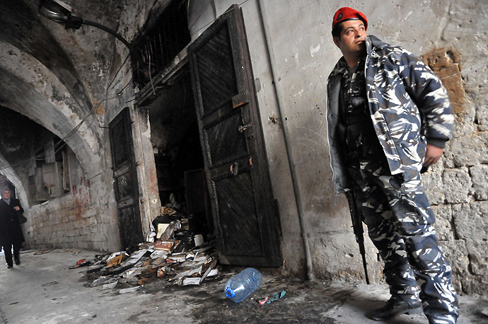 "A Lebanese soldier stands guard, on January 4, 2014 in north Lebanon's city of Tripoli, outside a decades-old library owned by a Greek Orthodox priest that was torched after ""a pamphlet was discovered inside one of the books that was insulting to Islam and the prophet Mohammad"" said a source, who spoke to AFP on condition of anonymity. (AFP Photo)"